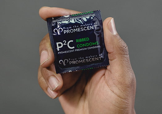 Promescent ribbed condom in hand.