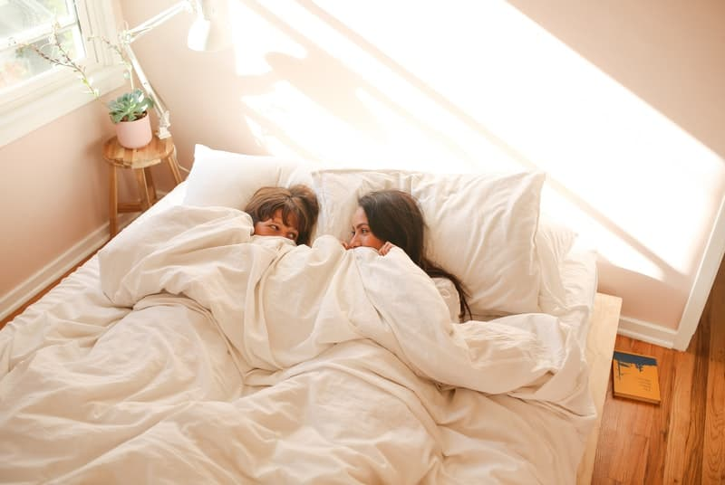 Two women laying in bed excited about scissoring