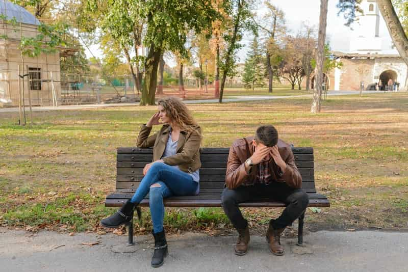 Unhappy couple sitting on a park bench