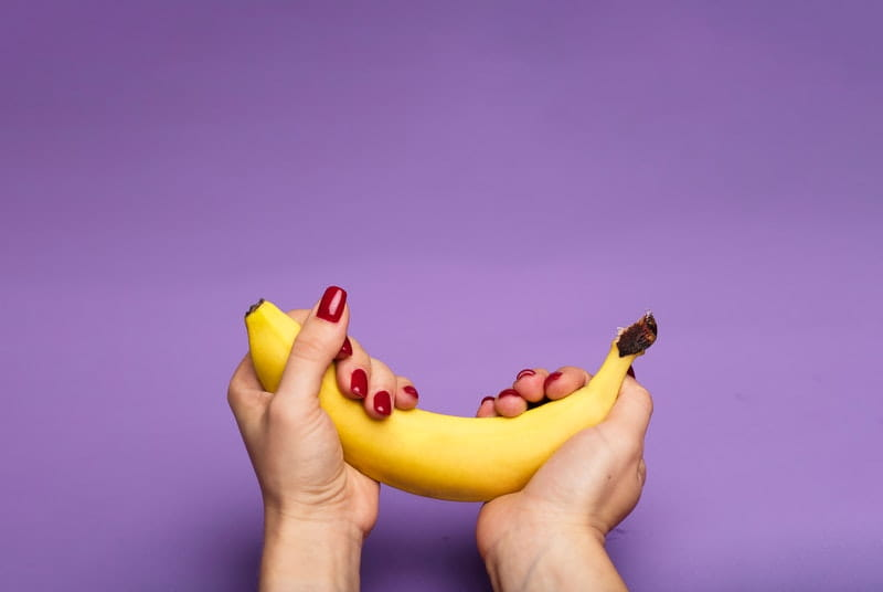 Woman gently cradling banana is if it were a penis