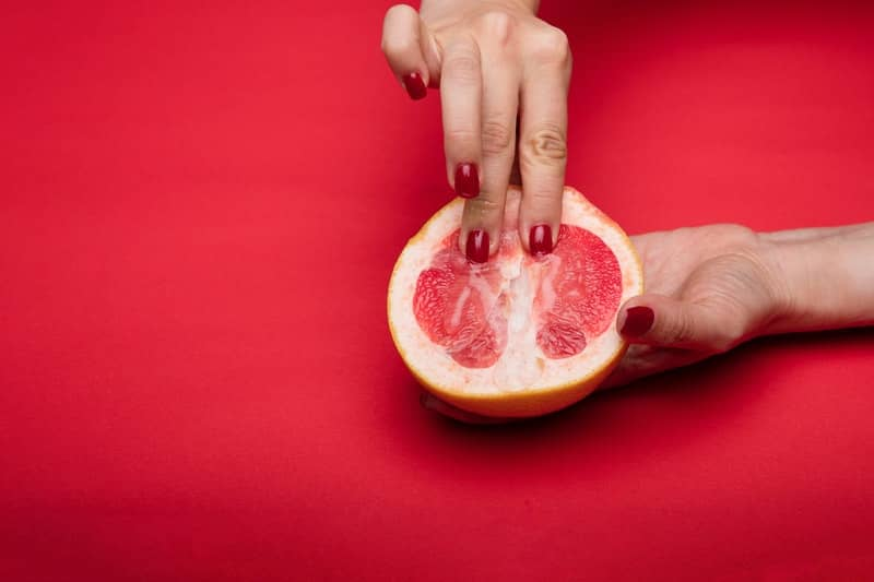 Yoni massage being demonstrated on a grapefruit half