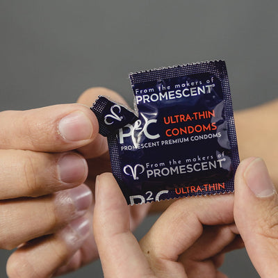 A Promescent ultra thin condom being shown slightly opened from it plastic packaging