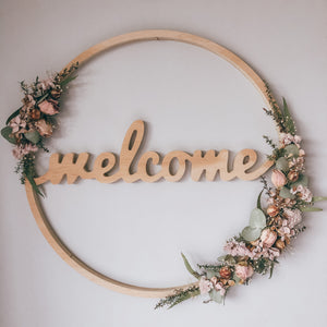 Circular wooden wreath with the word welcome in the centre, decorated with soft pink and pastel green coloured flowers and foliage