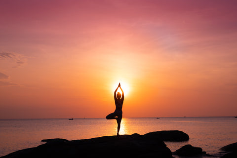 Woman in yoga pose in front of sunrise
