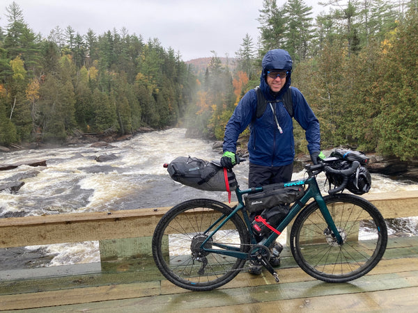 Kieran, bundled in rain gear, and wet, stands with his bike on a bridge over a raging river.
