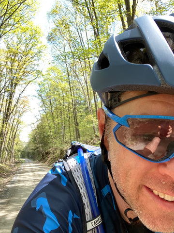Kieran's face, smiling at the camera, with a forest-lined gravel road behind him