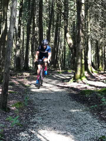Kieran, cycling down a tiny gravel path in the middle of a forest