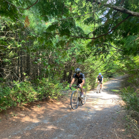 Cyclists ride down a green corridor on an isolated backroad
