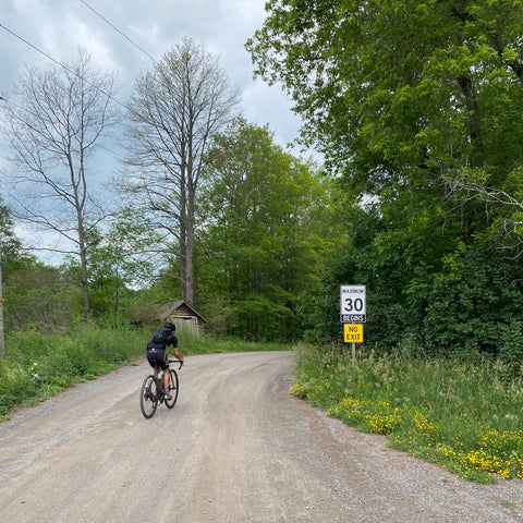"""A cyclist rides down a backroad marked """"No Exit"""""""