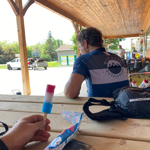 The cameraperson sits at a picnic table holding a popsicle while a cyclist sits in front of them with their back to the camera