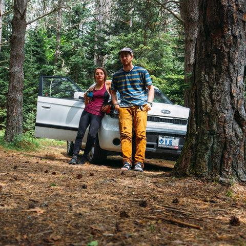 Tori and Justin lean on a car at their campsite