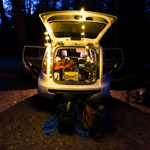 A hatchback with the rear open shows the camping gear inside