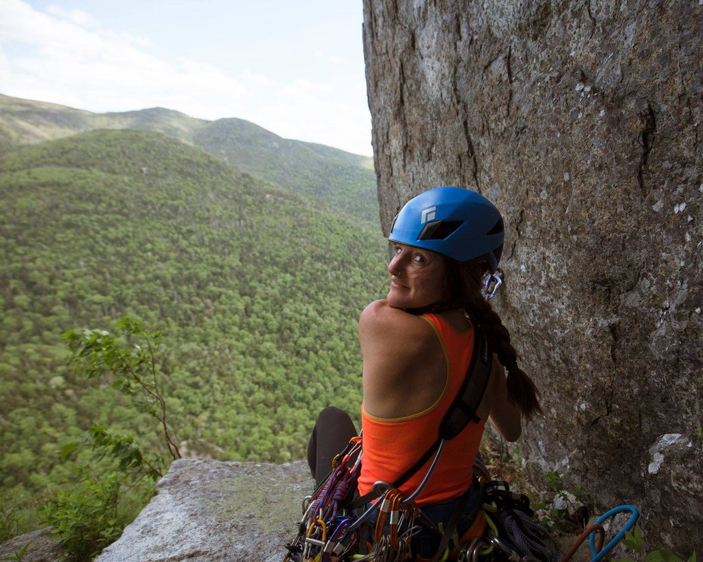 Tori Silvera, in rock climbing gear, looks out over a view of the mountains