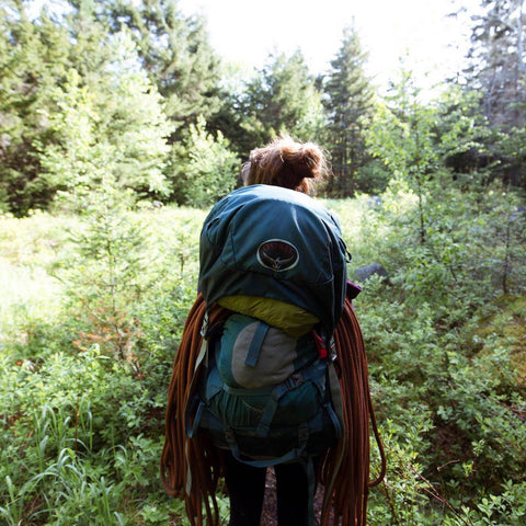 Tori, with her back to the camera, walks into the woods wearing a large backpack