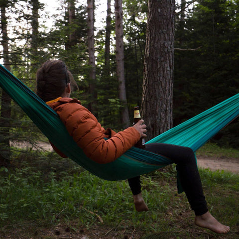 Tori Silvera sits in a hammock in the woods, with a beer in her hand