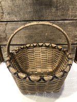 "Classic Williamsburg basket, expertly woven  by master basket weaver, Mary Ann Williams.  Approximately 2.5 qt size, dark brown accent cord, other accent colors may be available.  Perfect for holiday gifting, gathering berries or small garden vegetables, flowers and herbs.  Possibilities are endless...  locally made in the Hudson Valley.   Approximately 11""w x 5""h (12""h to top of handle), round."