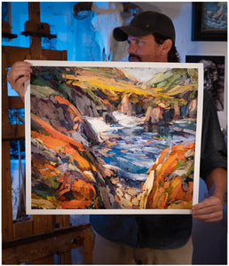 Artist Sean Diediker holding a print of his artwork Red Cliffs on Highway 1 in Big Sur California.