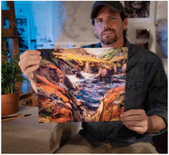 Painter Sean Diediker holding a print of his art Red Cliffs on Highway 1 in Big Sur California as part of Canvasing The World TV show on PBS.