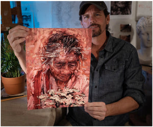 Artist Sean Diediker with a fine art reproduction print of The Flower Woman The Beggar Woman Ubud Bali Indonesia.