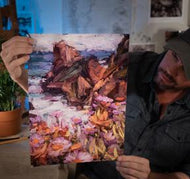 Sean Diediker fine art painter holding a print of a landscape from Big Sur episode of Canvasing The World TV show.
