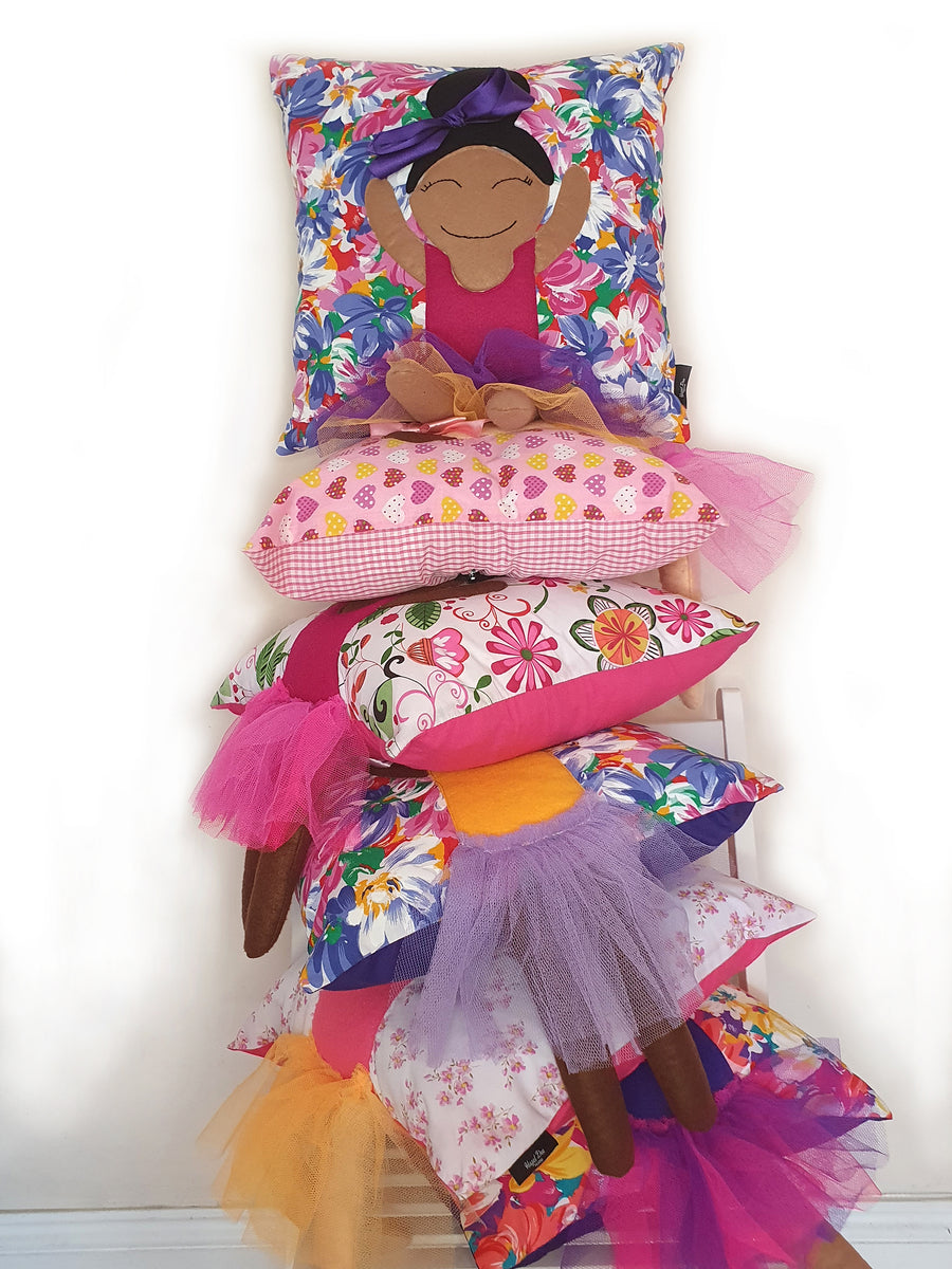 A stack of Hazeldee Home Kids Munchkin Character Cushions in a variety of prints, skin-tones and hairstyles