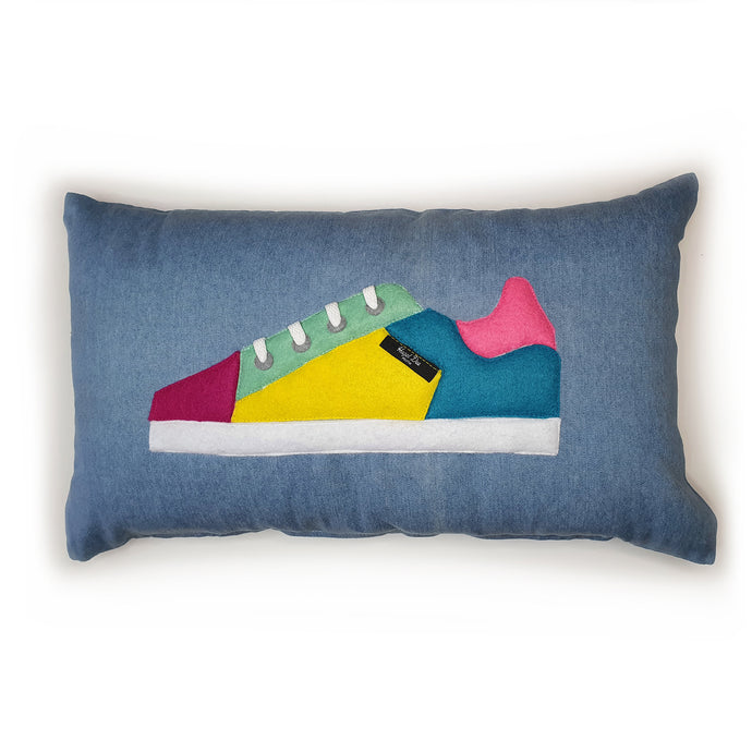 Hazeldee Home Handmade bold colour-block trainer cushion, rectangular bolster shape with real laces trim on a blue denim base.  A great conversational trainer cushion for kids and grown ups alike!  Bring some fun and colour into your space with this handmade cushion with a trainer with laces detail!  Colour-block sneaker trainer cushion with Hazeldee Home label detail.  Approximately 12
