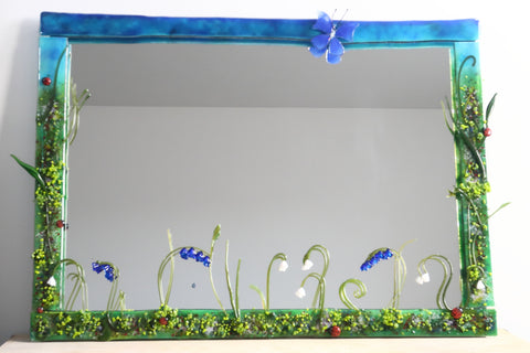 handmade glass mirror frame inspired by flower meadows with ladybirds, blue butterfly and glass snowdrops and bluebells