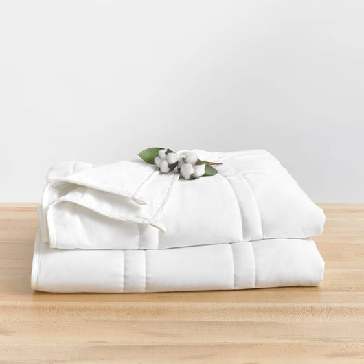 White Weighted Throw Blanket folded sitting on a Table