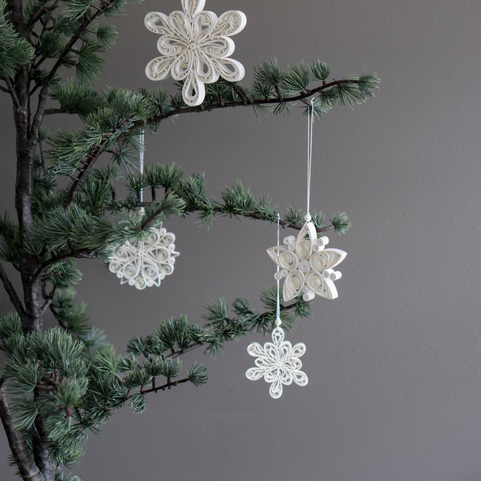 Snowflake paper tree decorations top: light; middle: heavy, regular; bottom: light, styled on a pine tree.