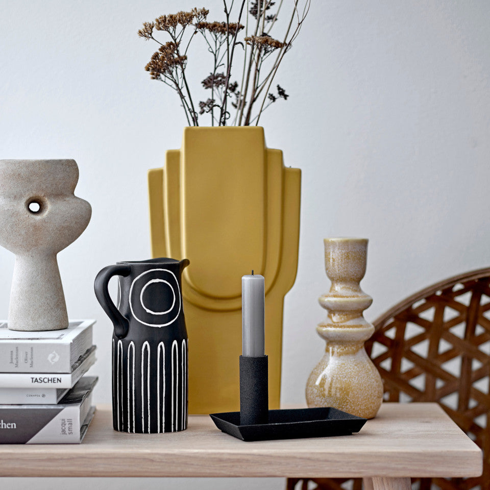 Troy vase, black terracotta jug shape, with white circle and narrow arch pattern, styled in front of the Ata vase, yellow stoneware, with candlesticks, books and decorative objects on a wooden table.
