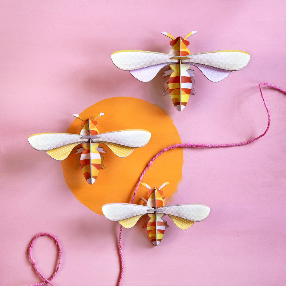 Honey bee wall decoration, set of 3, styled on a pink and orange wall.