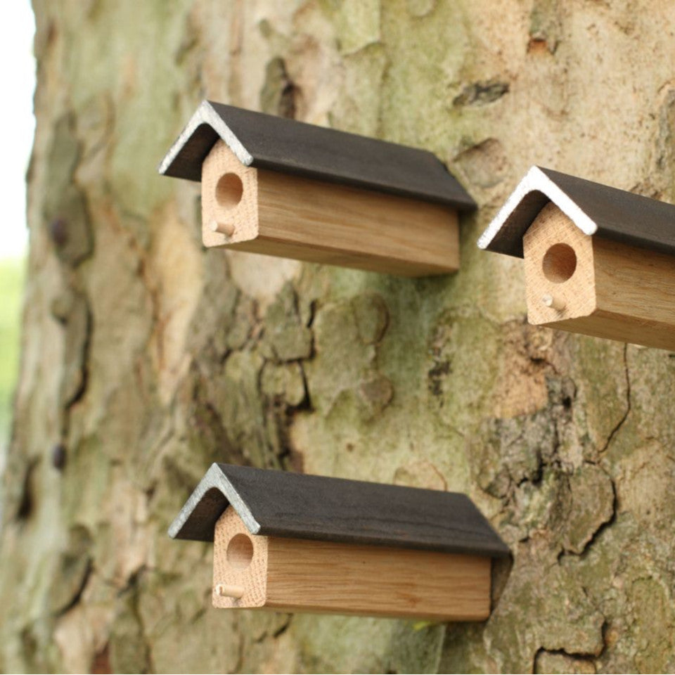 Bees Knees oak and steel solitary bee houses, set of three, styled on tree trunk.