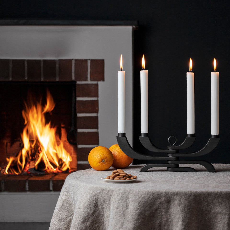Nordic 4-arm black candle holder, styled open on a table with a fire.