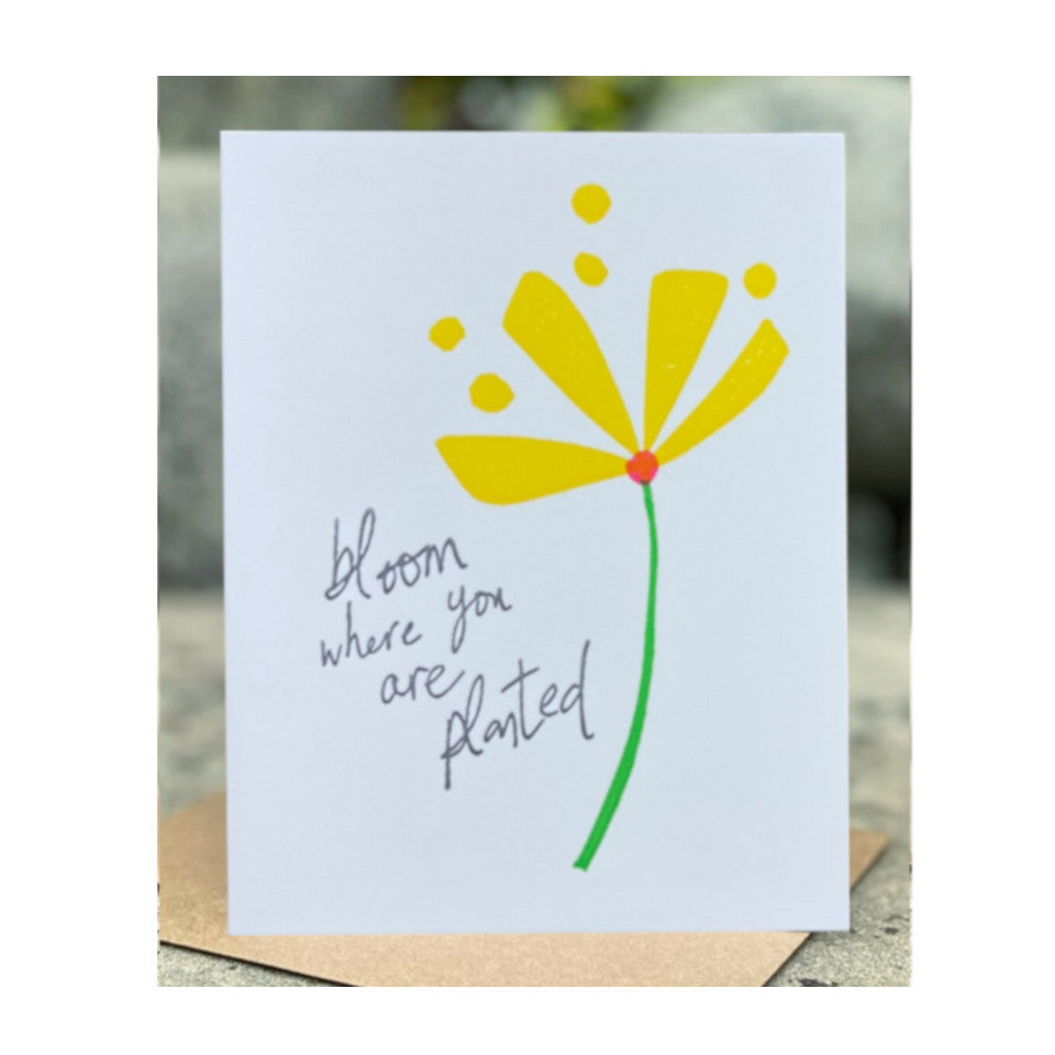 Bloom Where You Are Planted, grey text beside bright yellow flower with bright green stem, new home greeting card with brown 100% recycled envelope.
