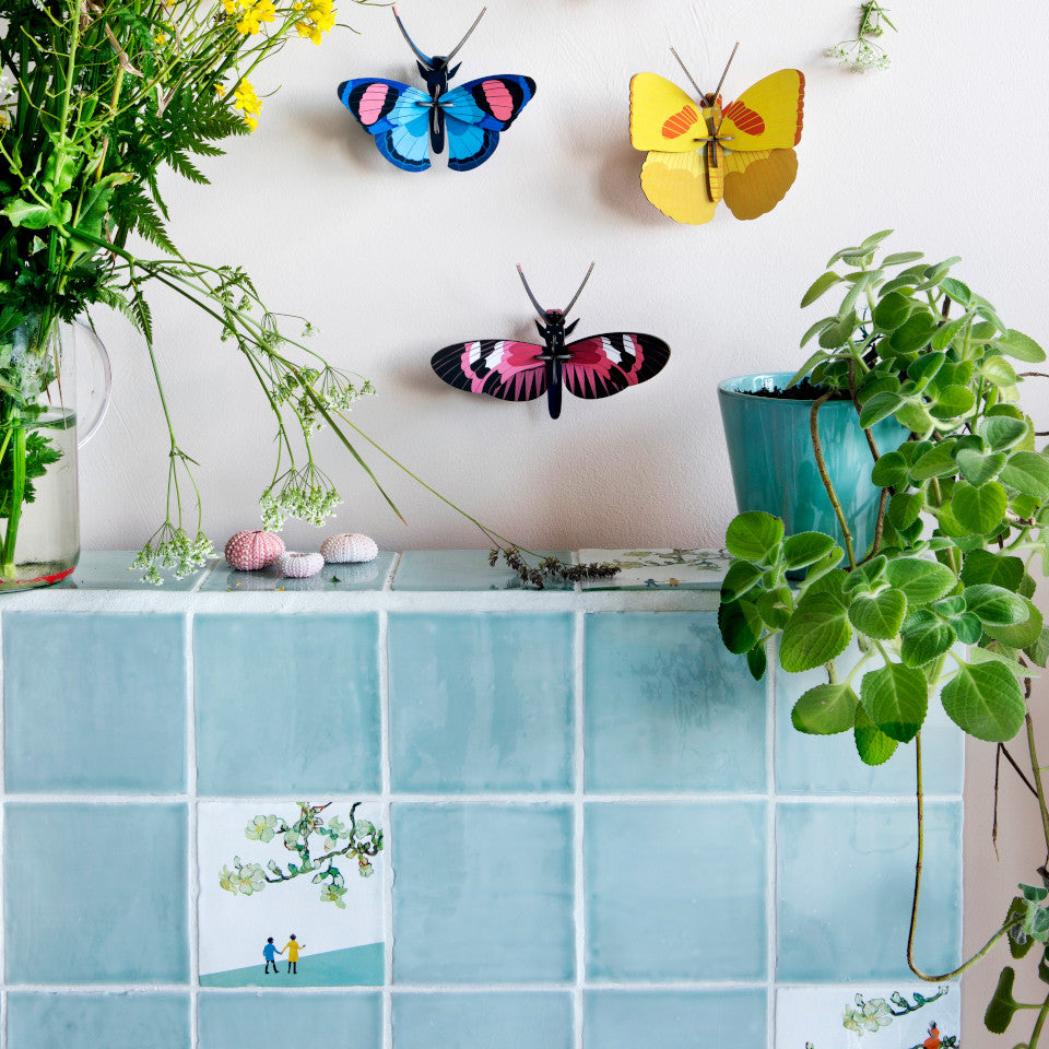 Peacock, Yellow and Longwing butterflies styled above a tiled wall with plants and flowers.