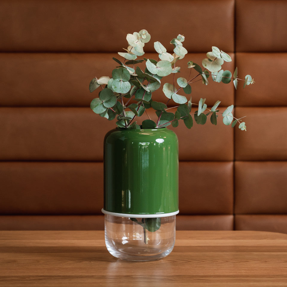 Capsule green/clear extending glass vasestyled with foliage on a wooden table.