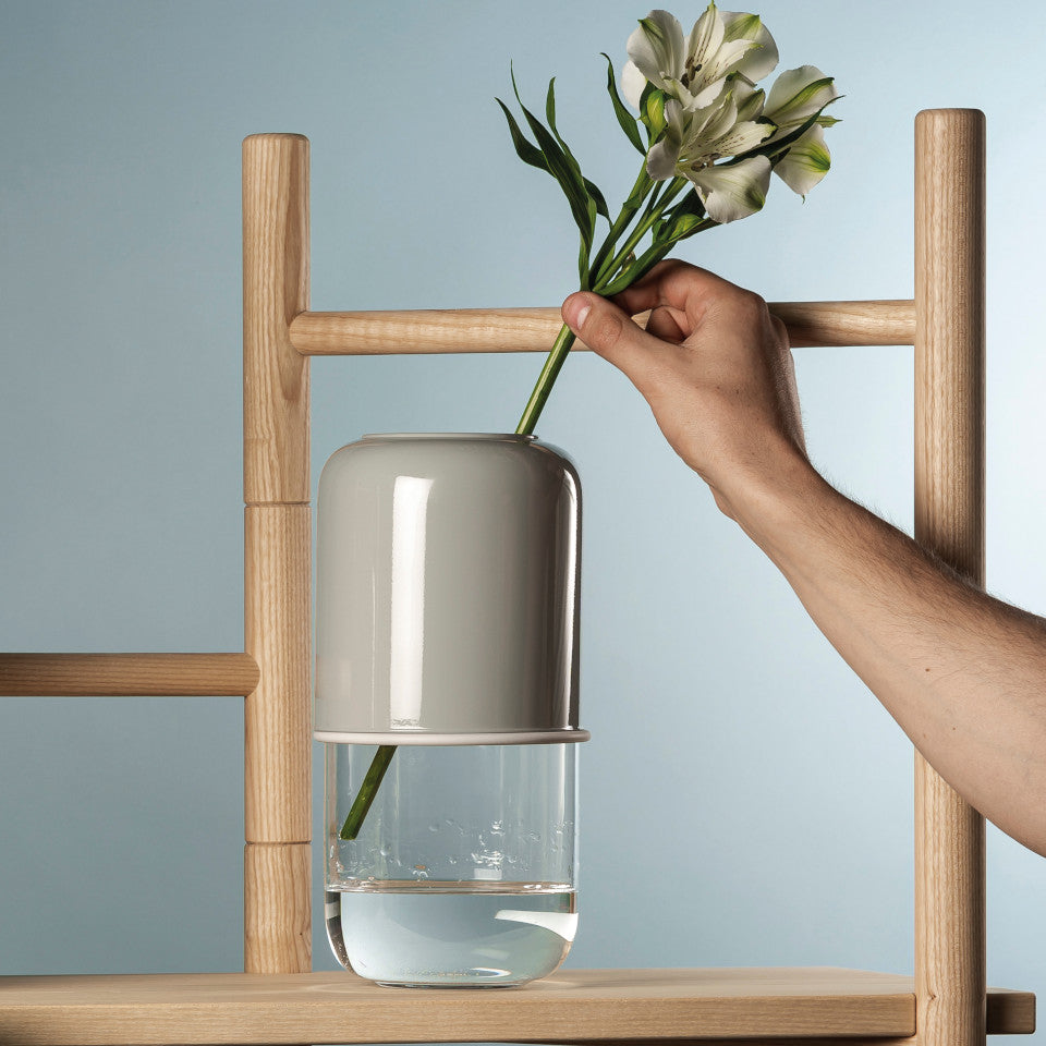 Capsule grey/clear extending glass vase, styled with a stem on a wood shelving unit.