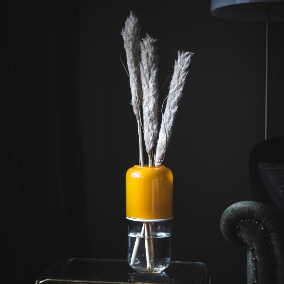 Capsule mustard/clear extending glass vase at it's full extent styled with pampas grasses on a glass side table..