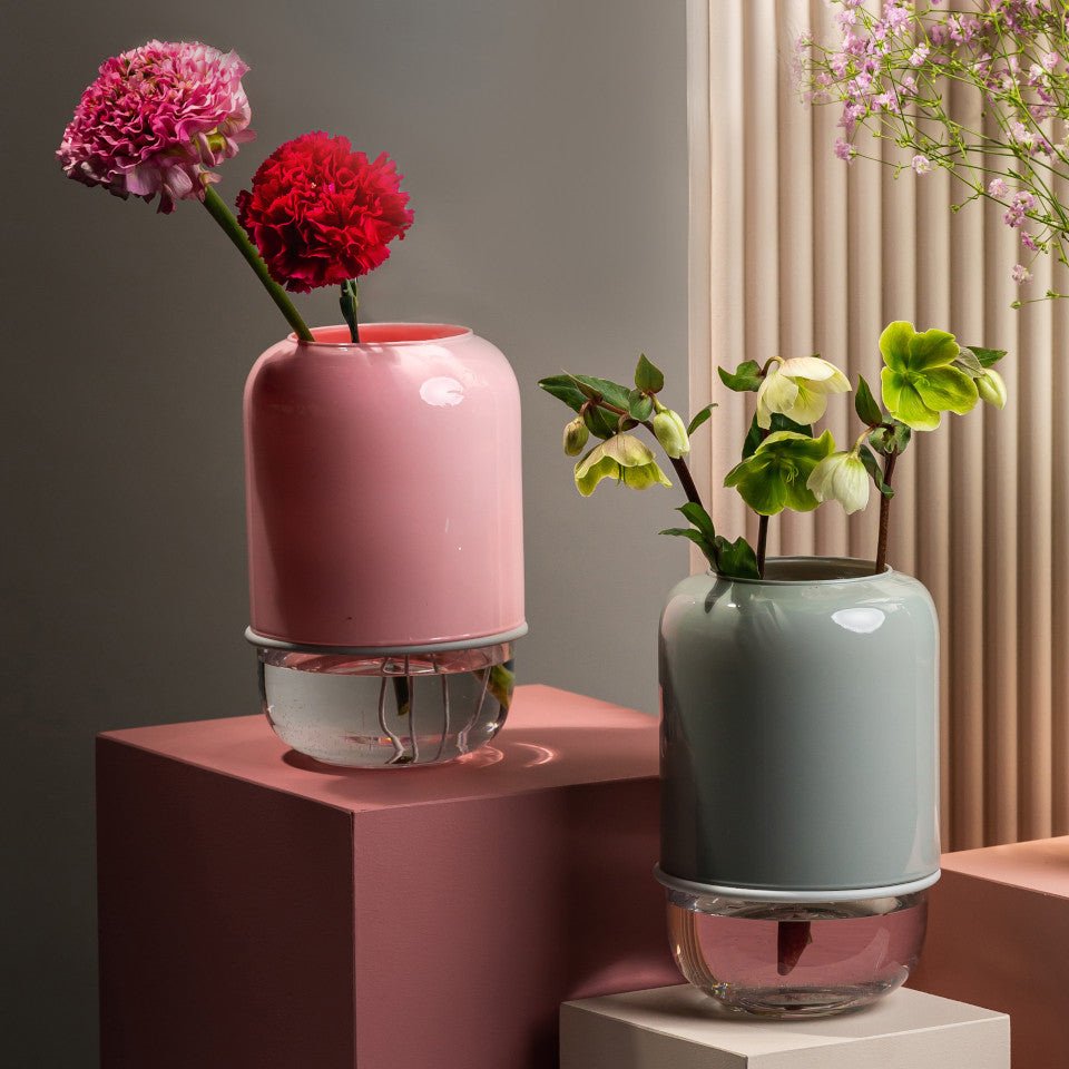 Capsule pink/clear and grey/clear extending glass vases styled with blooms on pink and grey display boxes.