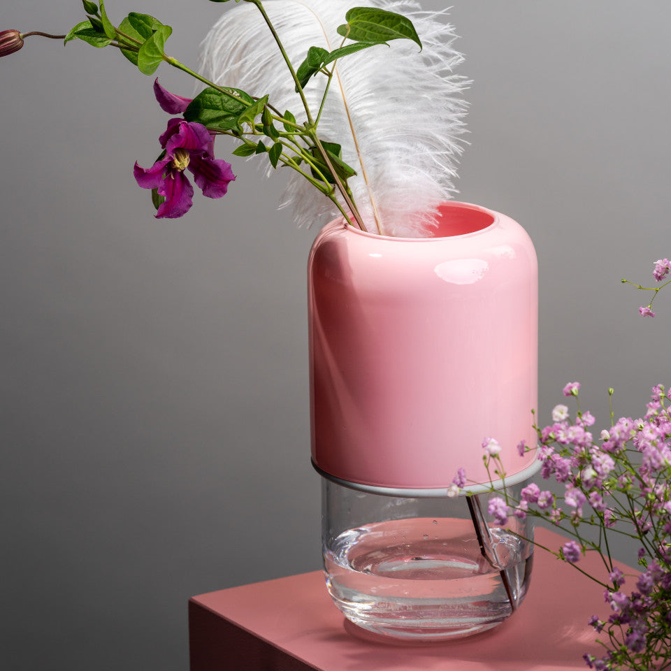 Capsule pink/clear extending glass vase, styled with blooms and a feather on a pink display box.