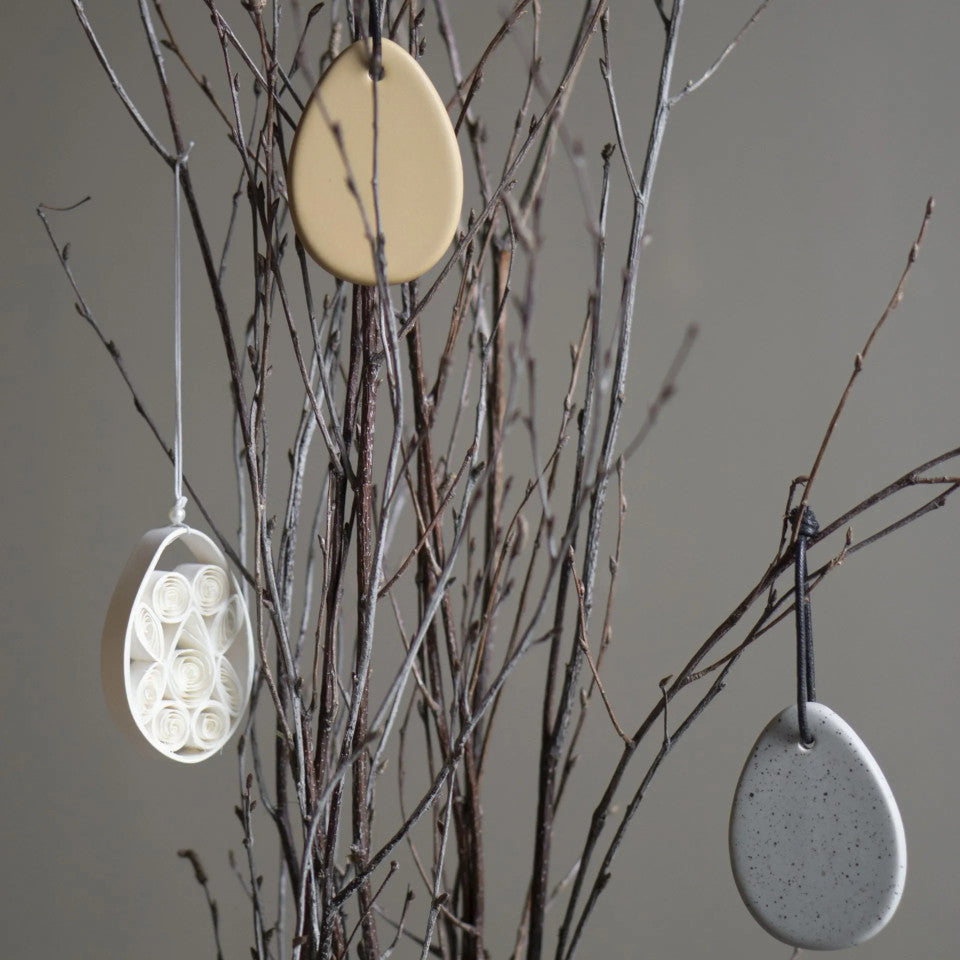 Easter egg flat ceramic Easter egg grey dot and ochre, styled on twigs with the quilled paper Easter egg hanging decoration.
