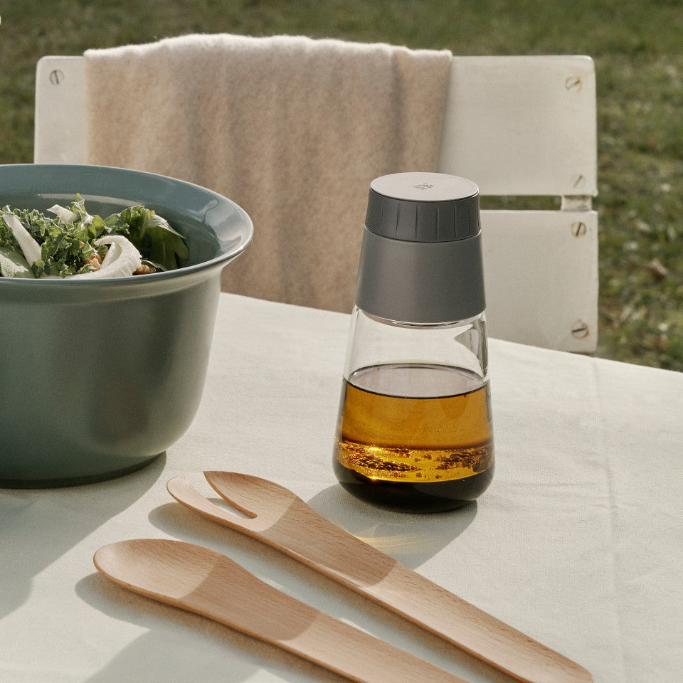 Shake-It by RigTig dressing shaker styled on garden table with salad and servers.