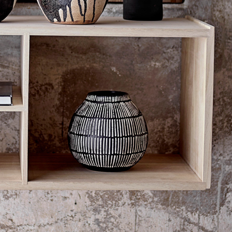 Elveda vase, onion-shaped black stoneware with rows of white verticle lines, styled in a wooden cube shelving unit..