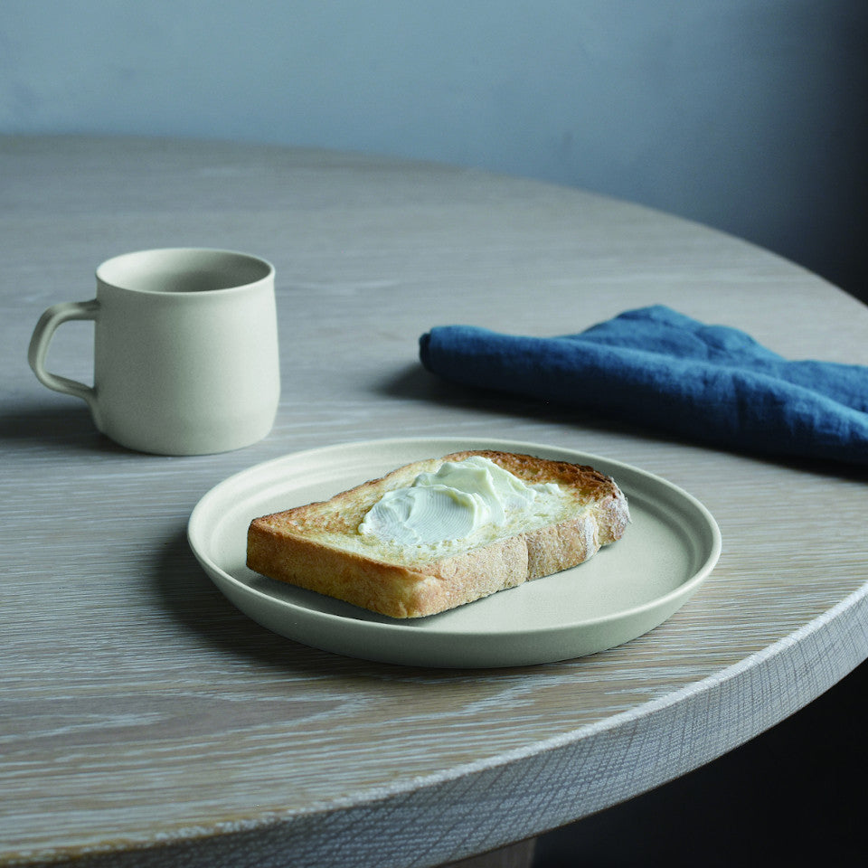 Fog ash white mug and 16 cm plate styled with toast and a napkin.