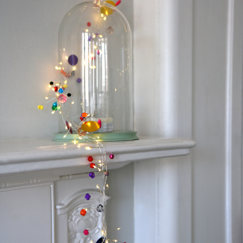 Folklore light chain - mains operated, styled draped around a bell jar and cascading from a mantlepiece.