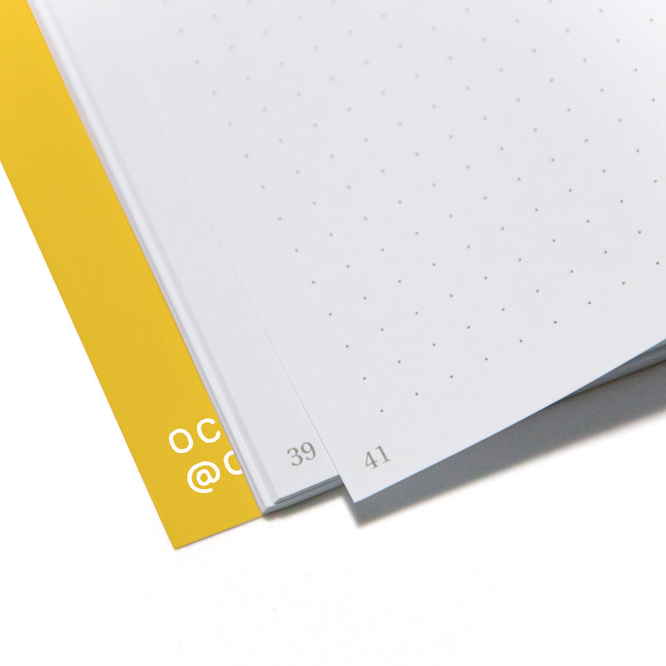 FUN yellow notebook with white lettering, detail of page corners.