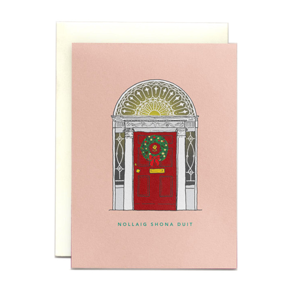 Red Dublin Georgian door and fanlight on a pink background Christmas card with 'Nollaig shona duit' (Happy Christmas to you) and a Christmas wreath hanging on the door.