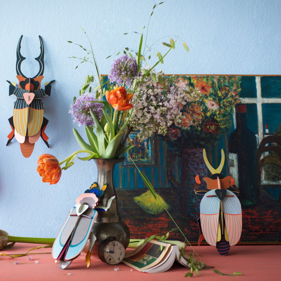 Giant Stag, Rhinoceros and Tiger beetle cardboard wall decorations, styled with a vase of flowers and a painting.