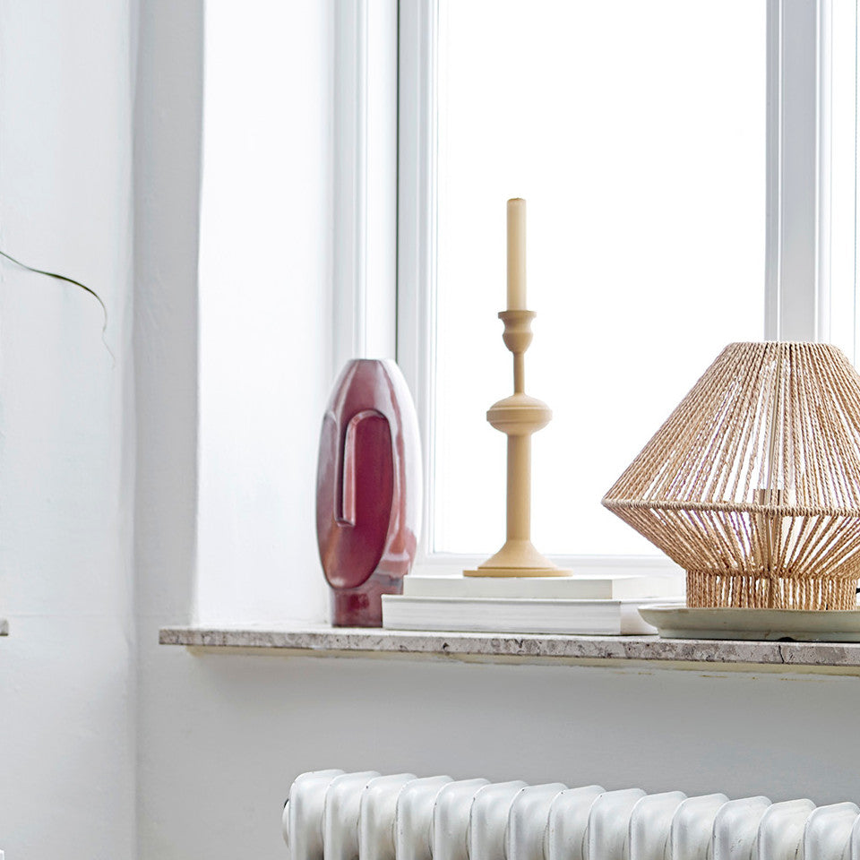 Idica candlestick, yellow metal in a 'turned wood' style, styled on a windowsill with other decorative items and books.