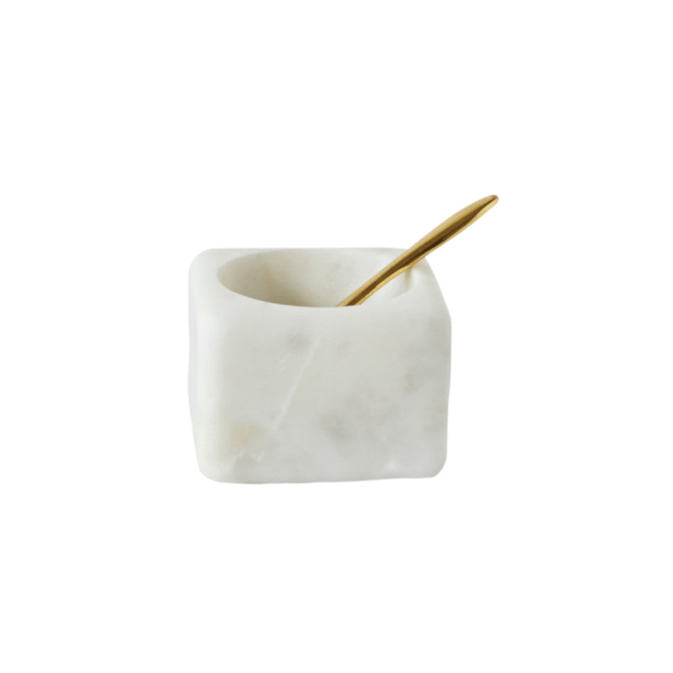 White marble salt jar with brass spoon.